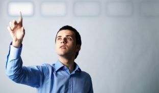 Image of young businessman pointing at virtual button