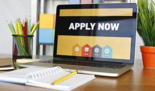 laptop with apply now written on screen