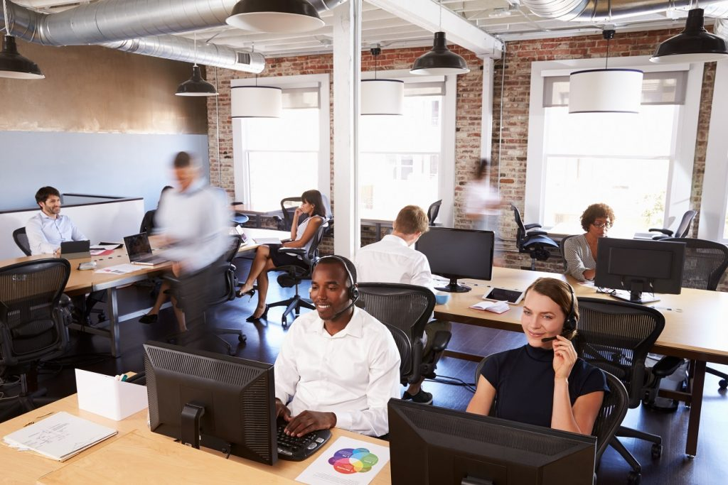 Image of staff speaking on headsets in a busy call center