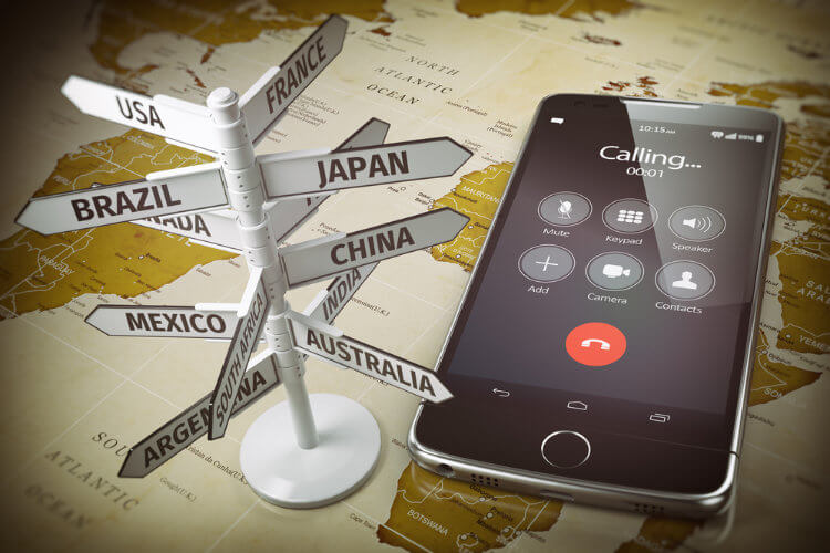 Phone and sign pointing to different countries on a map